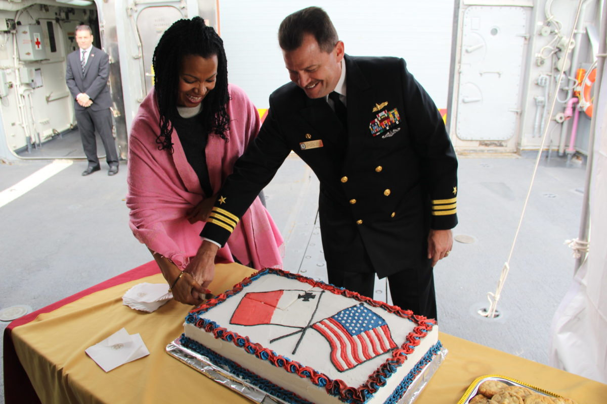 Then-U.S. Ambassador to Malta Gina Abercrombie-Winstanley, and Cmdr. Christopher Follin, commanding officer of the guided-missile frigate USS Simpson (FFG 56), cutting a cake during a reception during the ship's port visit to Malta. (U.S. Navy)