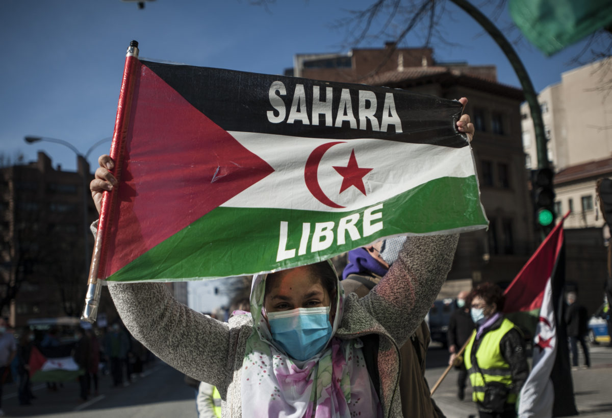 A Saharawi woman holds a Sahara flag during the demonstration. (Photo by Elsa A Bravo/SOPA Images/Sipa USA via AP Images)