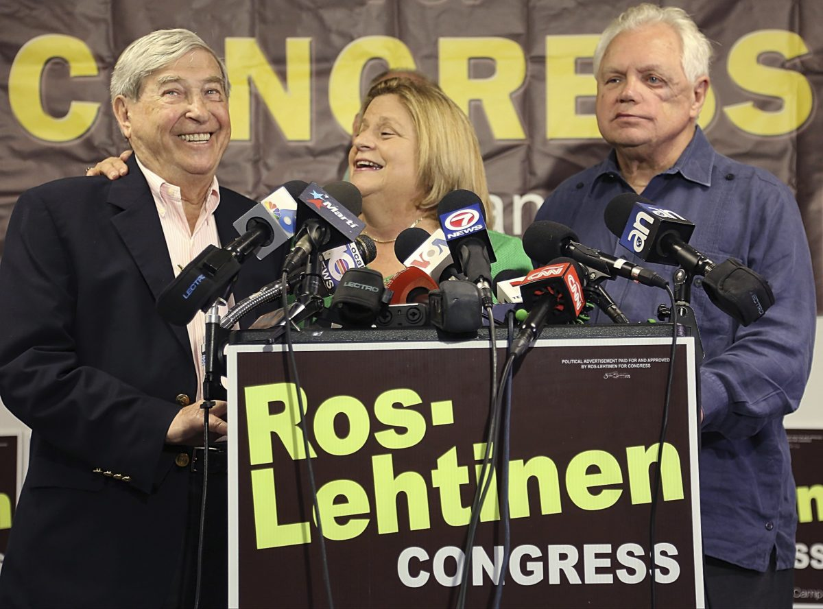 Former Rep. Ileana Ros-Lehtinen, center, reminds Holocaust survivor David Mermelstein, left, that her remaining days in Congress will be to fight for compensation for Holocaust survivors, Monday, May 1, 2017, as she stands with her husband, Dexter Lehtinen, right, at the podium while she gave a statement regarding her retirement from Congress, in Miami. (Carl Juste/Miami Herald via AP)